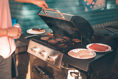 man standing by BBQ with meat cooking