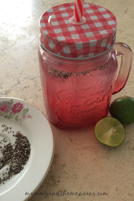 A Glass Of Lemonade Made With Limes And Chía Seeds Next To A Plate With Some Chia Seeds And Some Limes