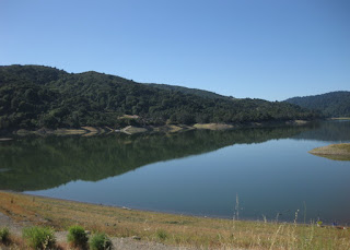 Hills reflected in the calm water of Lexington Reservoir, view from the dam, Los Gatos, California