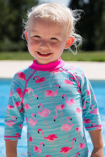 A grinning toddler in a long sleeve SPF sun suit