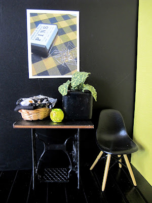 Modern dolls' house miniature scene of a vintage sewing table and Eames chair in front of a black wall displaying a poster with vintage pins on a checked fabric.