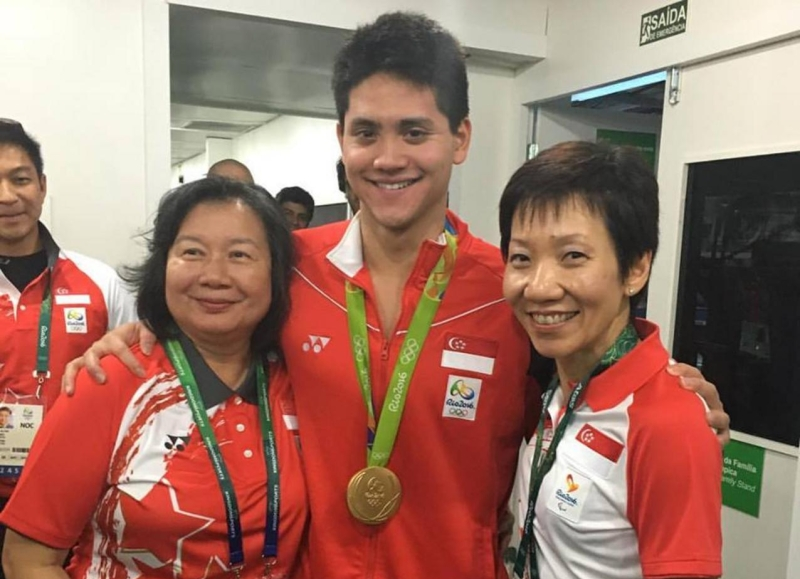 Joseph Isaac Schooling, 约瑟林 Yuē sè lín (center) after winning the gold medal with his mother Yan Jin Mei, 严锦美 yán jǐn měi (left) and Minister of Culture and Youth, Community Grace Fu, 傅海燕 fù hǎi yàn (right) with Minister for Social and Family Development, Tan Chuan-Jin, 陈川仁 Chén chuān rén looking on at the far left.