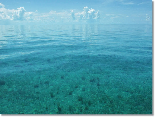 A flat calm turquoise ocean stretches to the horizon and bleeds into the turquoise sky.