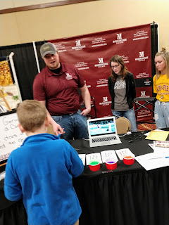 students from Morningside College lead a child through an activity involving a corn kernel and water beads of various colors to represent different things plants need such as water and nutrients at the 2019 Siouxland Garden Show