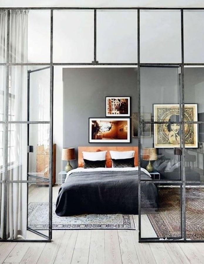 Pared de cabecero en gris en dormitorio con puertas de cristal y metal