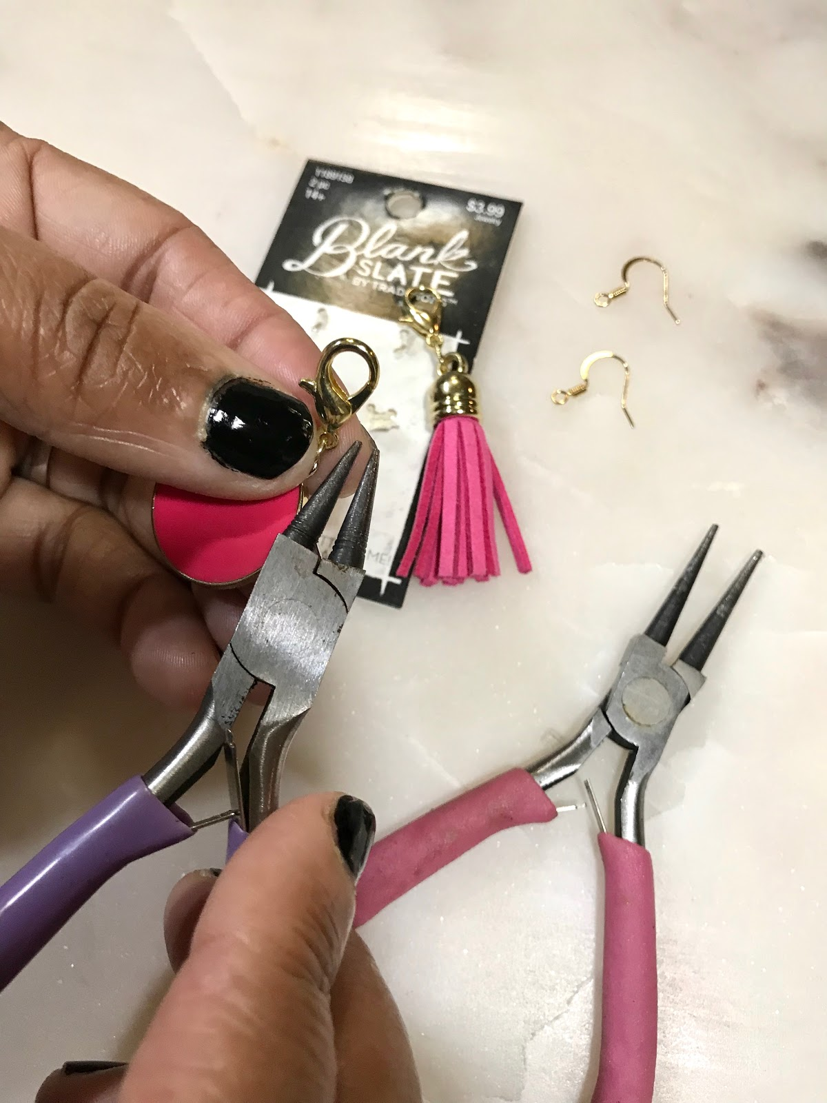 Image: Woman adding earring hook to earrings to make DIY project at home