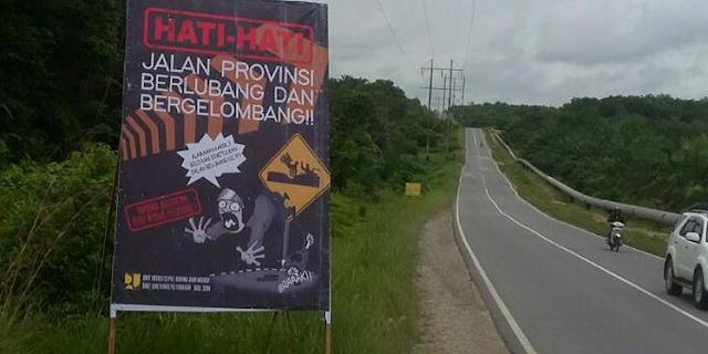 "baliho bertuliskan ""Hati-hati, Jalan Provinsi Berlubang dan Bergelombang!!"""