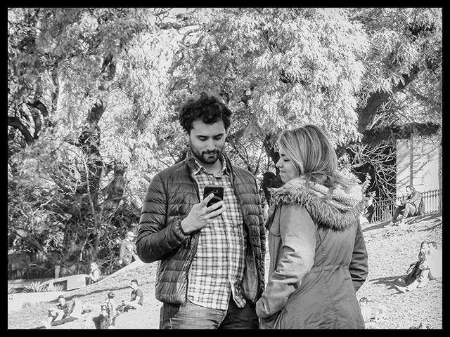 Hombre hojea su celular y su pareja sonríe.