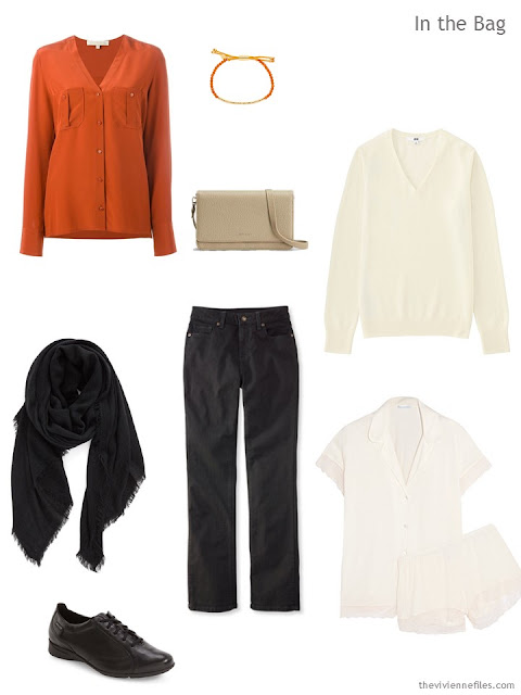 a travel outfit in orange, black, and sand
