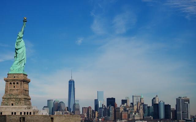 Die Skyline von New York vor blauem Himmel, im Vordergrund die Freiheitsstatue