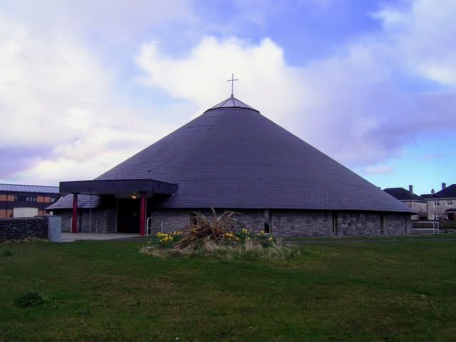 Photograph of a church built in the roundhouse / beehive style of building:  circular with pointed roof