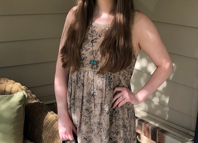 Model is wearing a brown paisley dress with natural-colored accessories.