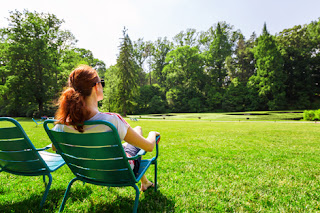 Photo of a Back View of a Woman Sitting in a Chair Looking at a Green Garden on a Summer Day