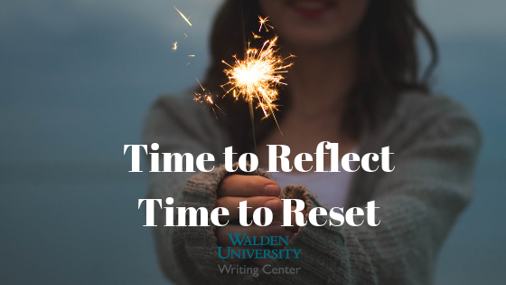 "Image of woman holding sparkler with text: ""Time to reflect; time to reset"""