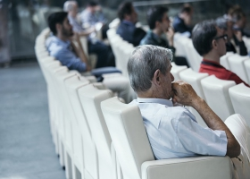 Listening to a speaker in an auditorium.