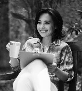foto com efeito preto e branco de Ana Esterque sentada de perna cruzada, sorrindo segurando copo e prancheta