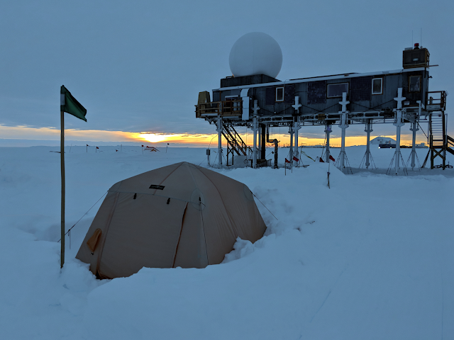Tent in front of a lodge on stilts in the Arctic