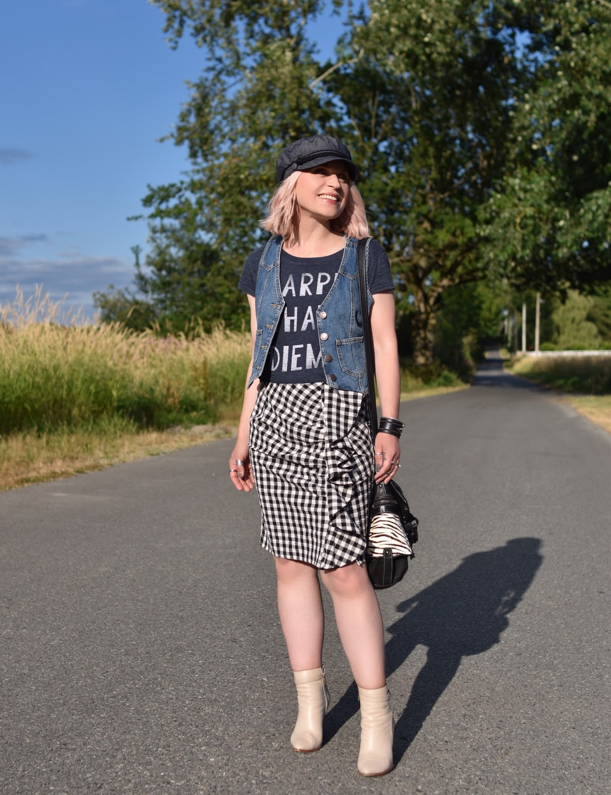 Monika Faulkner personal style inspiration - ruffled gingham skirt, graphic tee, denim vest, ivory booties, baker boy cap