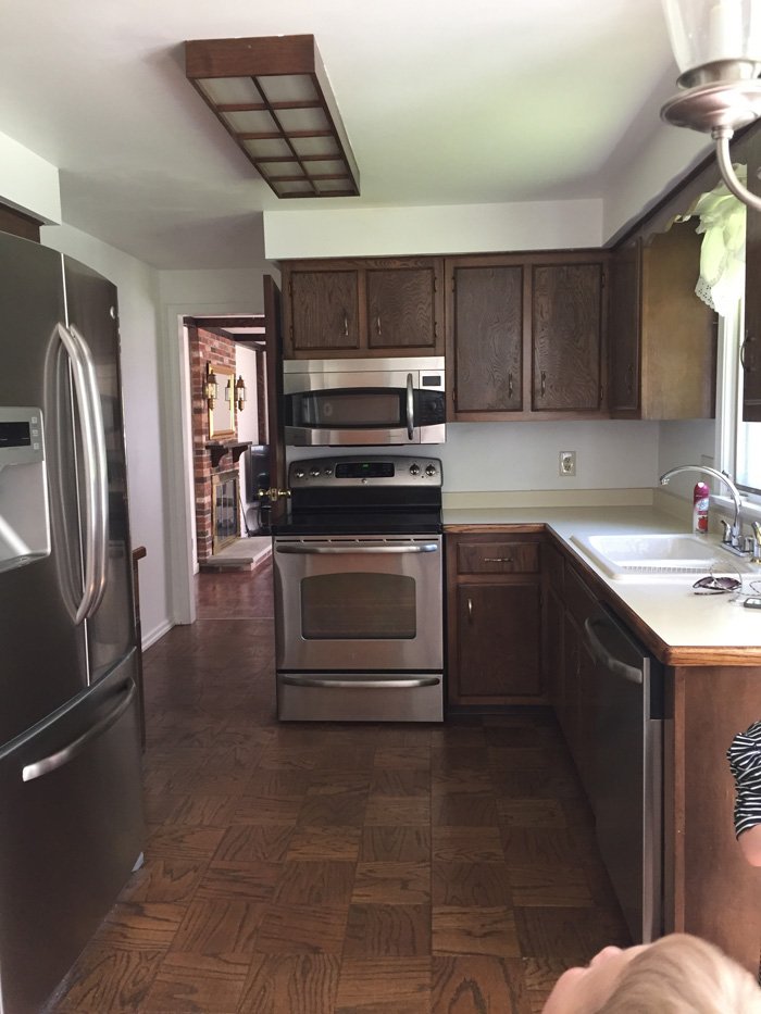 small colonial kitchen with dark stained cabinets and dated light fixtures