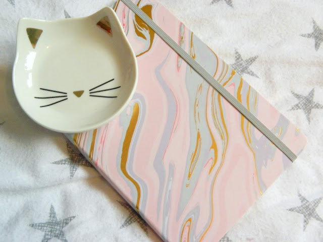 A white and gold cat trinket dish, and a colourful notebook