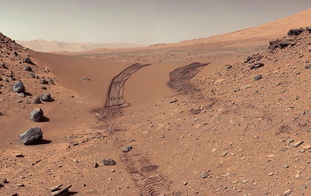 Tàu Curiosity quay lưng lại và thấy bánh xe của chính mình in dấu trên những nơi đã đi qua, được chụp bởi Mastcam gắn trên tàu trong sol 538 hay ngày 9 tháng 2 năm 2014. Tàu tự hành này đã bắt đầu đi qua khu vực này vào ba ngày trước. Ngọn đồi cao khoảng một mét, ở giữa có rãnh nhỏ thấp hơn và thuận tiện để tàu băng qua, được gọi là Rãnh Dingo. Hình ảnh: JPL-Caltech/MSSS/NASA.