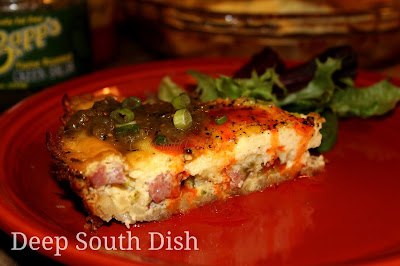 Smoked sausage quiche with onion, bell pepper and Swiss cheese in a hash brown crust, shown here served with a drizzle of hot sauce and Fire Roasted Green Salsa.