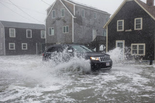 During this winter's nor'easters, high tides flooded the streets of Scituate, Massachusetts. The town and property owners, like others along the U.S. coasts, face rising costs to keep the ocean at bay. (Credit: Scott Eisen/Getty Images) Click to Enlarge.
