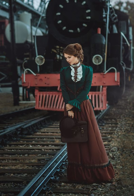 Steampunk woman wearing victorian clothing in brown and green, standing next to a steam train.