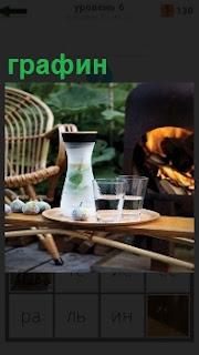 На столе стоит одинокий графин и рядом горит печка, кресло стоит и хорошая солнечная погода