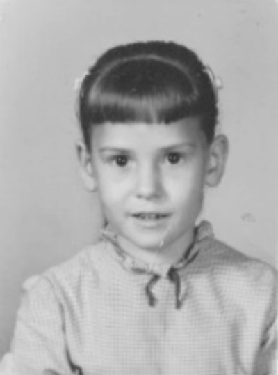 School Picture from 1957 of girl wearing gingham checked dress with hair in pony tail and bangs