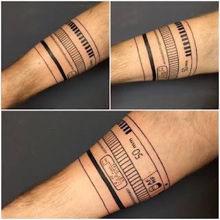 Tatuaje objetivo fotográfico alrededor del brazo