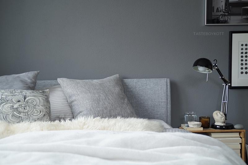 Schlafzimmer im Herbst einrichten und dekorieren in Grautönen und Weiß, mit vielen Wohntextilien für eine gemütliche Atmosphäre und Weinkiste als Nachttisch, Deko mit Fellen, Kissen, Decken, DIY Tonskulptur, Büchern, Ikea-Leuchte und Kerze