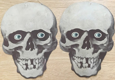 Two blue-eyed skulls circa 1920s with paper damage of crossbones removed