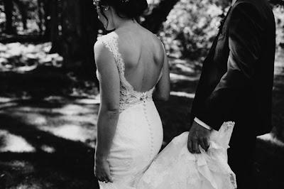 Novio ayudando con la cola del vestido a la novia