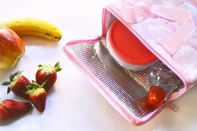 la bolsa abierta, dentro un tupper redondo y una botella, hay frutas fuera de la bolsa