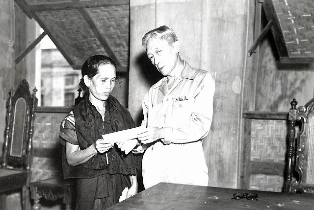 Governor Modesto Castillo hands a check from the United States to Mrs. Simeona Marquez to compensate for losses suffered from an accidental blast caused by stored explosives at Base R, Batangas, Luzon, P.I. Taken 20 March 1947.