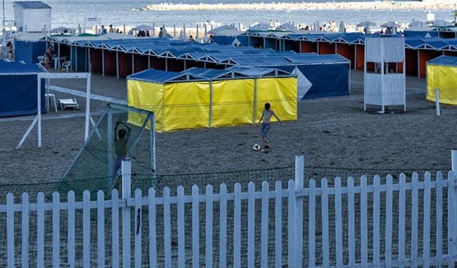 Una pequeña cancha de fútbol de piso de arena y dos pibes jugando en la playa..