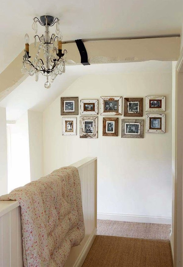Cottage chic landing with vintage paisley eiderdown and nicely arranged photo frames on the wall
