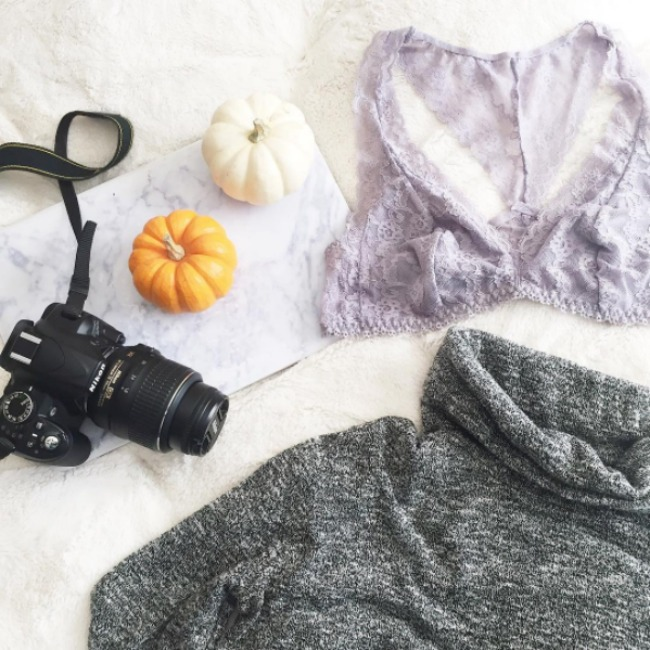 A fashion flat lay with a lavender victorias secret lace bralette, a gray marbled cowl neck sweater, a Nikon D3100 DSLR camera, pumpkins, and a marble laptop case.