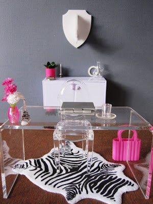 One-twelfth scale modern miniature office in shades of grey, white and hot pink. On the floor is a zebra-skin rug, and on the wall is a perspex rhino trophy head.