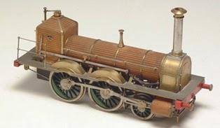 Maqueta realizada en hierro y cobre de la locomotora. Un gran cilindro central, con tres ruedas a cada lado, las delanteras de menor tamaño. Destaca la alta chimenea en el frontal.