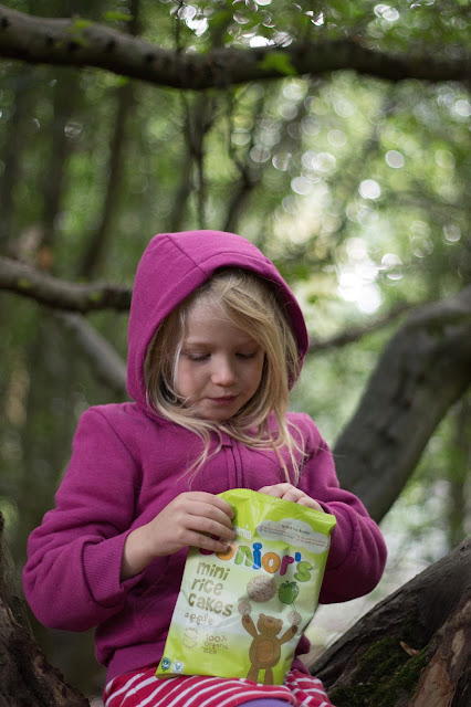 A girl in a pink hoody sits in a tree with a bag of mini rice cakes