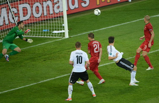 Germany striker Mario Gómez heads the ball to score against Portugal