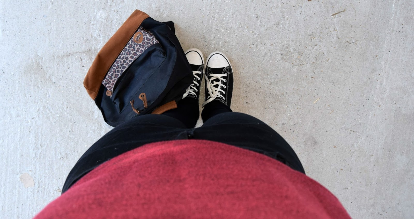 Looking down on an outfit of a dark red top, black skinny jeans, black and white converses and a black MI backpack with a leopard print front pocket
