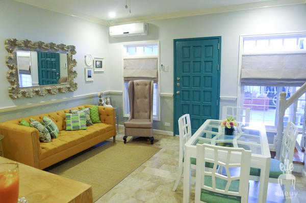 living and dining room of a colorful small apartment with beach theme, yellow sofa and teal door