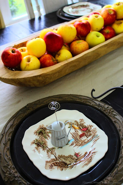 Wooden plate charger with black, brown and cream plate on a black table with beige table runner. Wooden dough bowl filled with apples on top. Fall Decor, Autumn Decorating, Table Decor, Cottage, Country, Natural Decor, apple tablescape rosevinecottagegirls.com