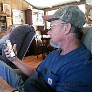 Jimmy sitting in a recliner holding a cell phone in his hand while looking at it.