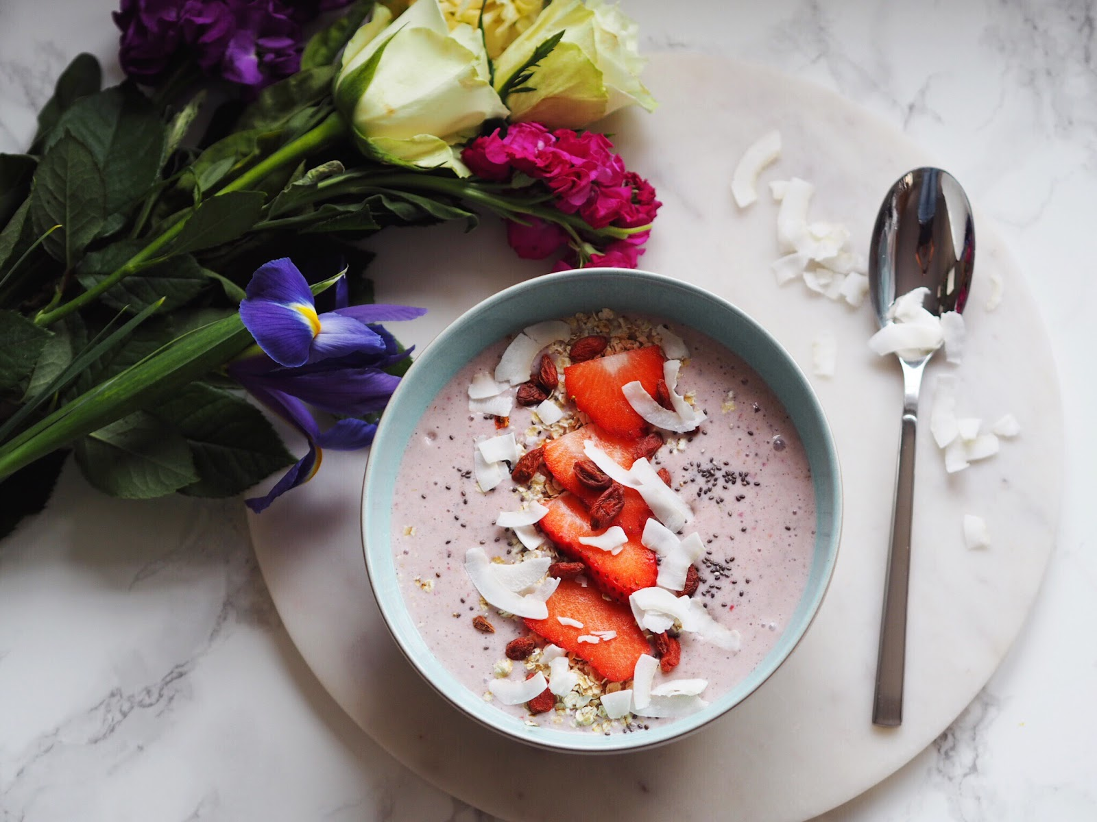 Chia Berry smoothie with flowers and spoon in flat lay