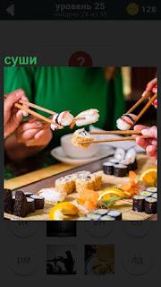 За столом палочками люди едят приготовленное суши