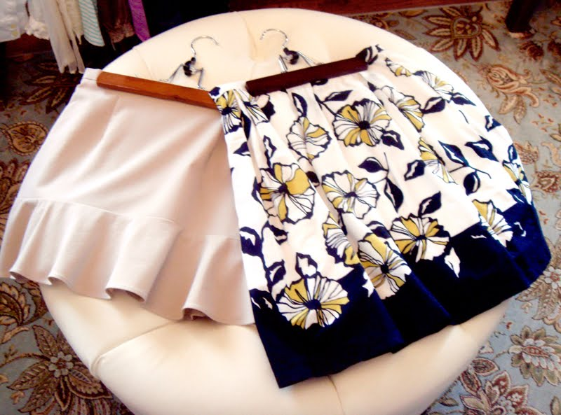Two skirts on ottoman. One beige with ruffles and the other printed with black and yellow floral design.